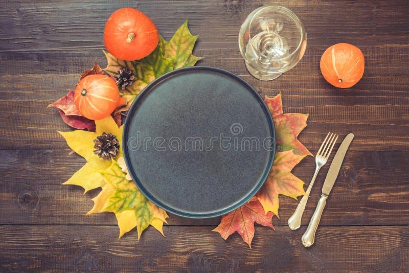 秋天和感恩天与下落的叶子、南瓜、黑盛肉盘和葡萄酒利器的桌设置在褐色 免版税库存照片
