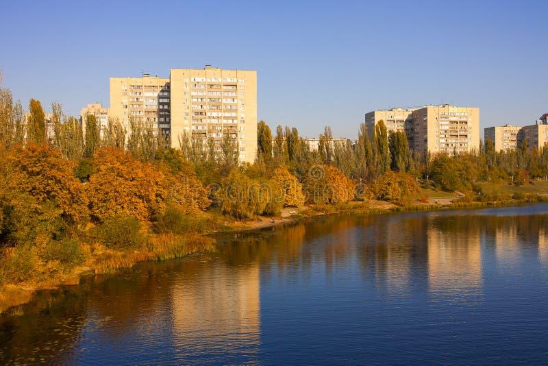 秋天在有黄色和橙树的河反映的城市风景在它的银行 免版税库存照片