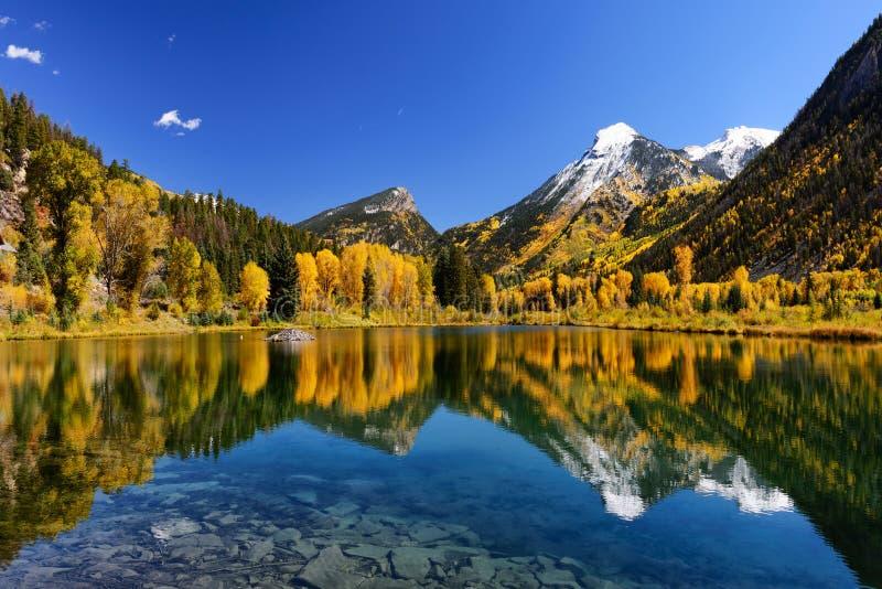 秋天在清楚的仍然湖的颜色反射 免版税库存图片
