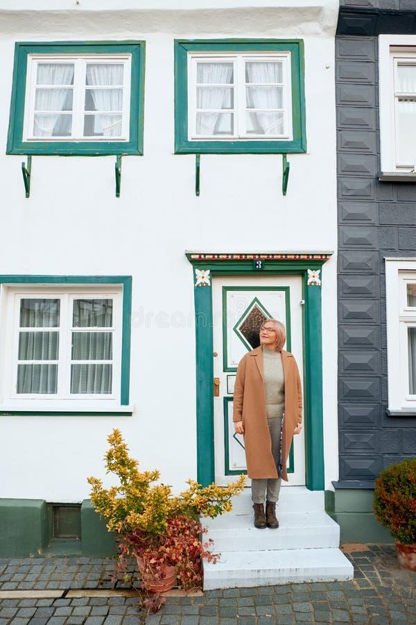 秋天外套的年轻美丽的女孩 在欧洲城市附近的旅行在秋天 快乐,微笑的夫人 老房子,铺st 免版税图库摄影