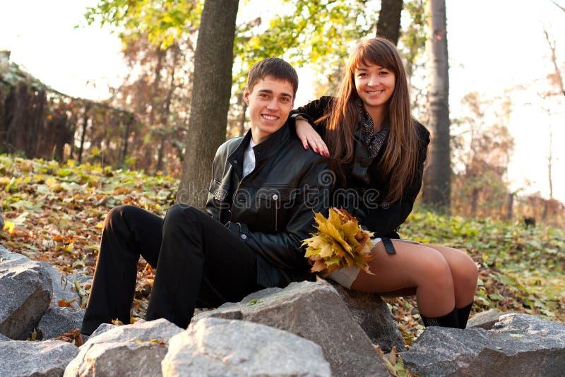 秋天夫妇愉快的户外微笑的年轻人 免版税库存图片