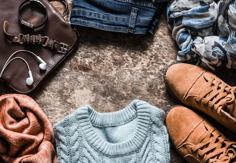 秋天套妇女` s衣物-绒面革鞋子,牛仔裤,编织了套头衫,围巾,书包,在木背景, t的辅助部件 免版税库存图片