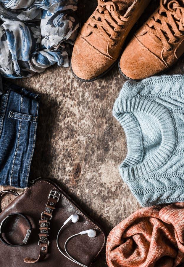 秋天套妇女` s衣物-绒面革鞋子,牛仔裤,编织了套头衫,围巾,书包,在木背景, t的辅助部件 库存照片