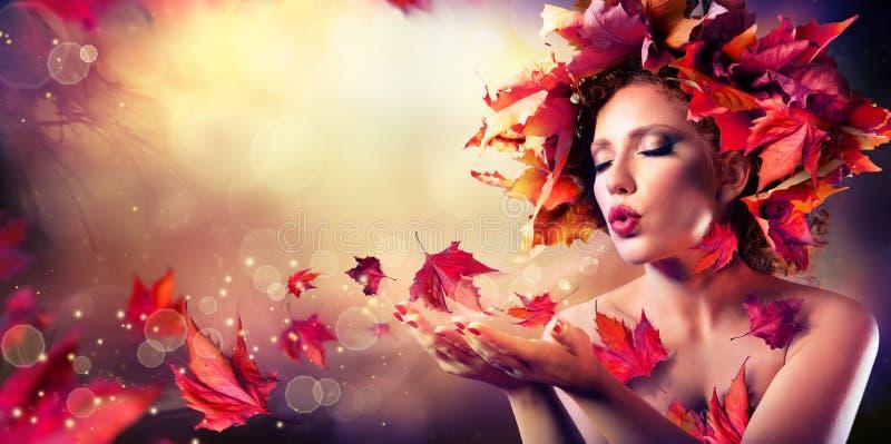 秋天妇女吹的红色叶子 库存图片