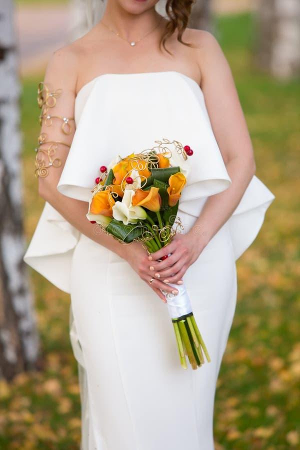 秋天婚礼花束在新娘的手上 库存图片
