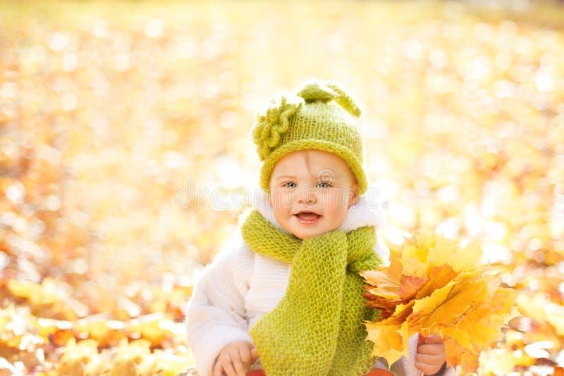 秋天婴孩,与黄色秋天叶子的愉快的孩子户外画象 库存图片