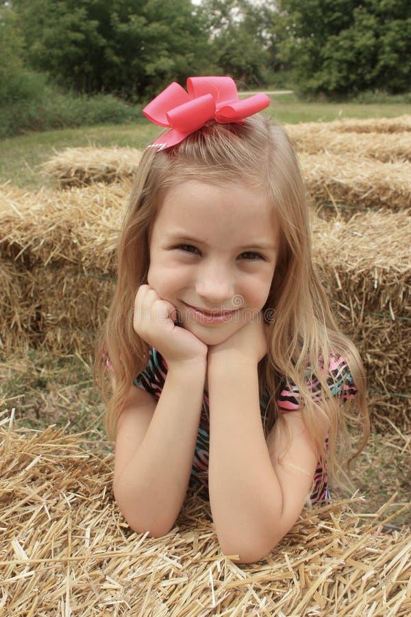 秋天干草捆的女孩 免版税库存图片