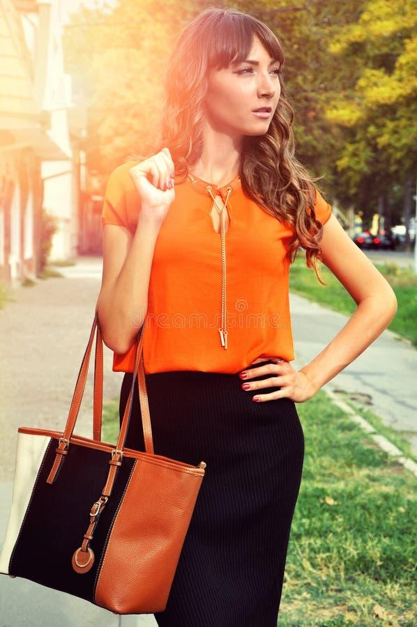 秋天成套装备颜色 穿着典雅的橙色衬衣黑色裙子和拿着五颜六色的皮包的老练深色的妇女 免版税库存照片