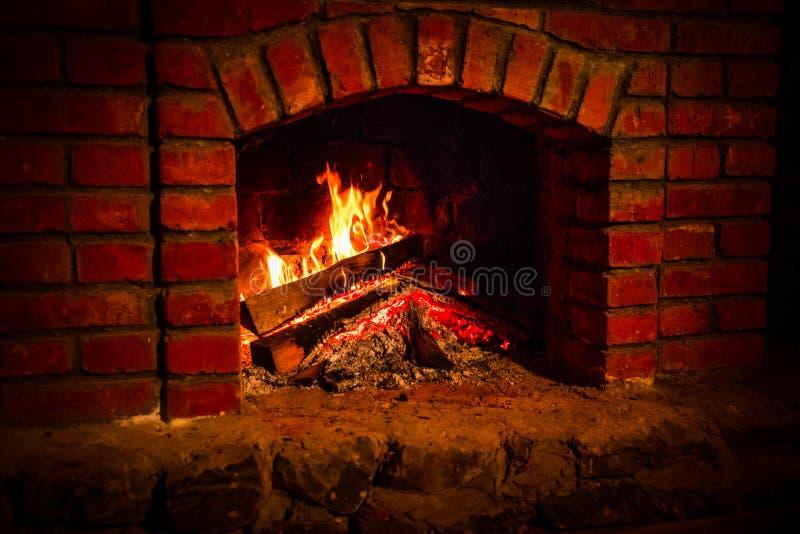 秋天或冬天灼烧的壁炉舒适晚上概念关闭 关闭灼烧的木柴射击在壁炉的 免版税图库摄影
