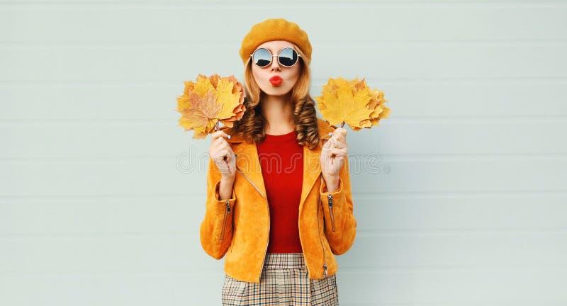 秋天拿着黄色枫叶的画象妇女吹送在法国贝雷帽的红色嘴唇甜空气亲吻摆在灰色墙壁 库存图片