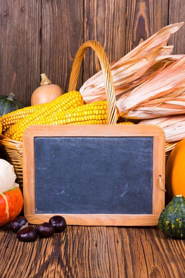 秋天收获节日动机用在一个篮子前面的各种各样的南瓜与在土气木背景的玉米棒子 免版税库存照片
