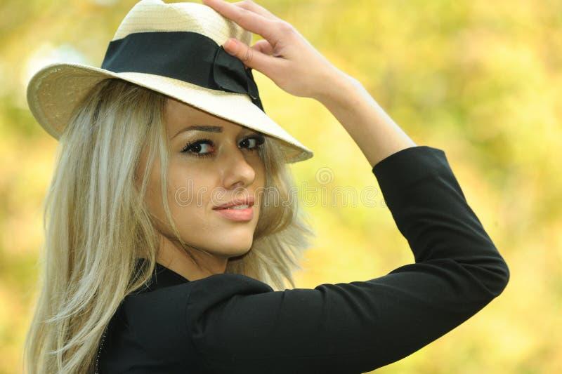 秋天时尚画象微笑的妇女佩带的帽子 免版税库存照片