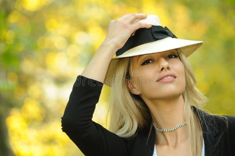 秋天时尚画象微笑的妇女佩带的帽子 免版税库存图片
