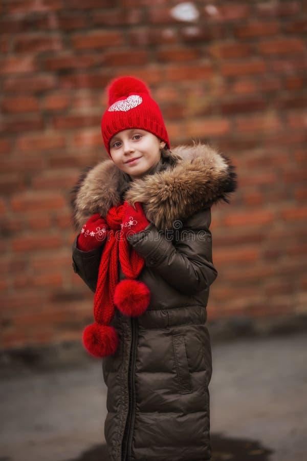 秋天时尚 孩子女孩秋季的穿戴外套 看有敞篷和毛皮的女孩面孔逗人喜爱的发型时兴的秋天外套 免版税图库摄影