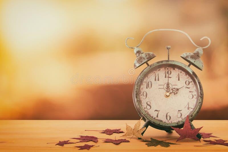 秋天时间变动的图象 后退概念 烘干叶子和葡萄酒闹钟在土气木桌上 免版税库存照片