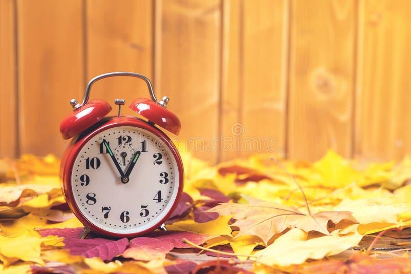 秋天时间变动 下落的叶子和老闹钟在土气木背景 秋叶 秋天时间 免版税库存照片