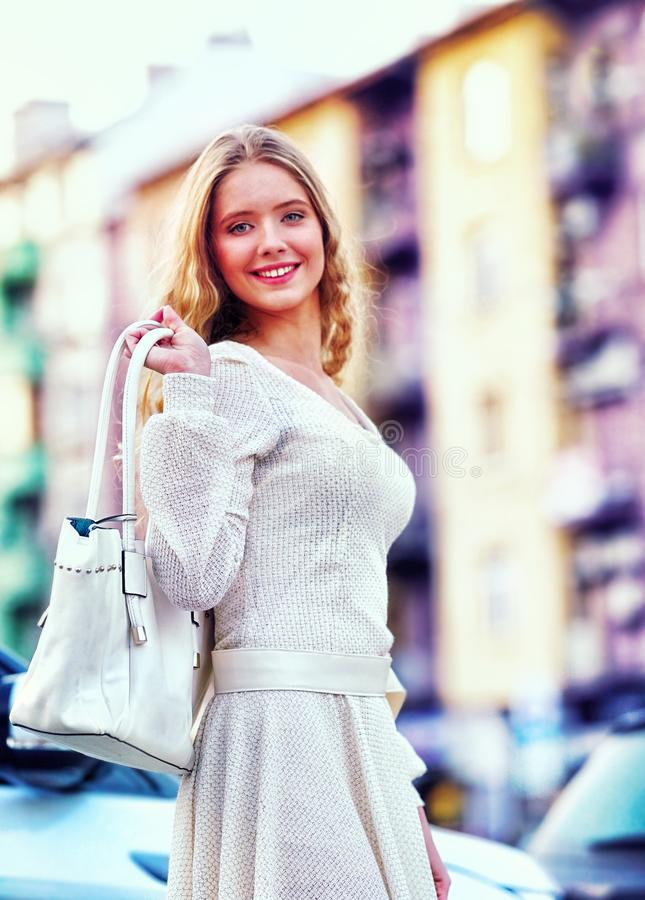 秋天春天礼服的时尚妇女有汽车城市街道的 库存图片