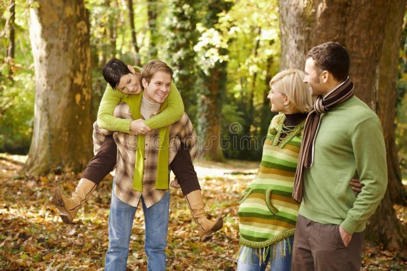 秋天有朋友的乐趣公园年轻人 免版税库存照片