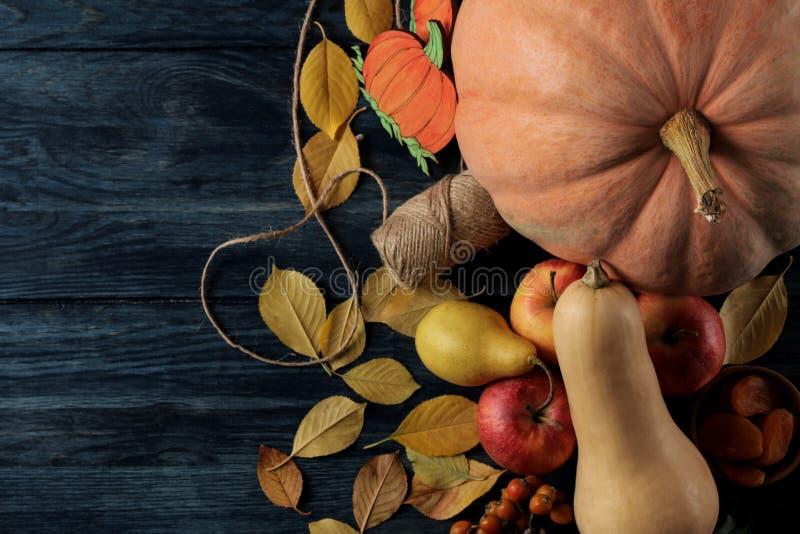 秋天构成用南瓜和秋天结果实用苹果,并且梨和黄色在一张深蓝桌离开 免版税库存照片