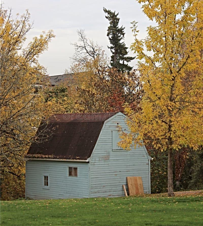 秋天树之前包围的蓝色谷仓 图库摄影