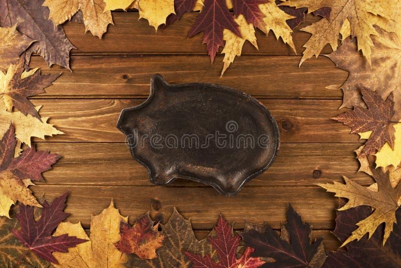 秋天槭树离开在木背景,在生铁的猪在中心 库存图片