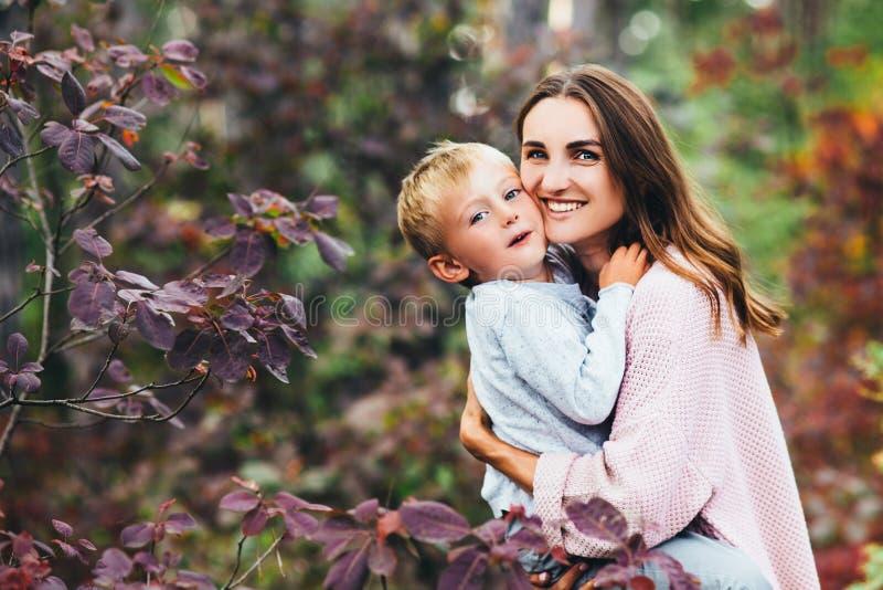 秋天步行的幸福家庭!走在公园和享受美好的秋天自然的母亲和儿子 免版税库存图片