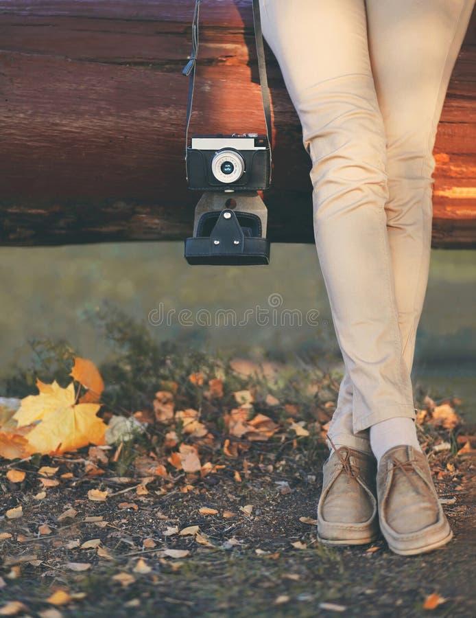秋天照片妇女和减速火箭的葡萄酒照相机与黄色枫叶特写镜头 免版税库存图片