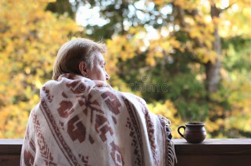秋天生活方式 羊毛格子花呢披肩的成熟妇女在阳台或ter 免版税库存图片