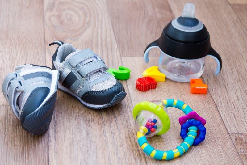 秋天的儿童的在木背景的鞋子和玩具与文本的地方 第一穿上鞋子婴孩如何选择大小 免版税库存图片