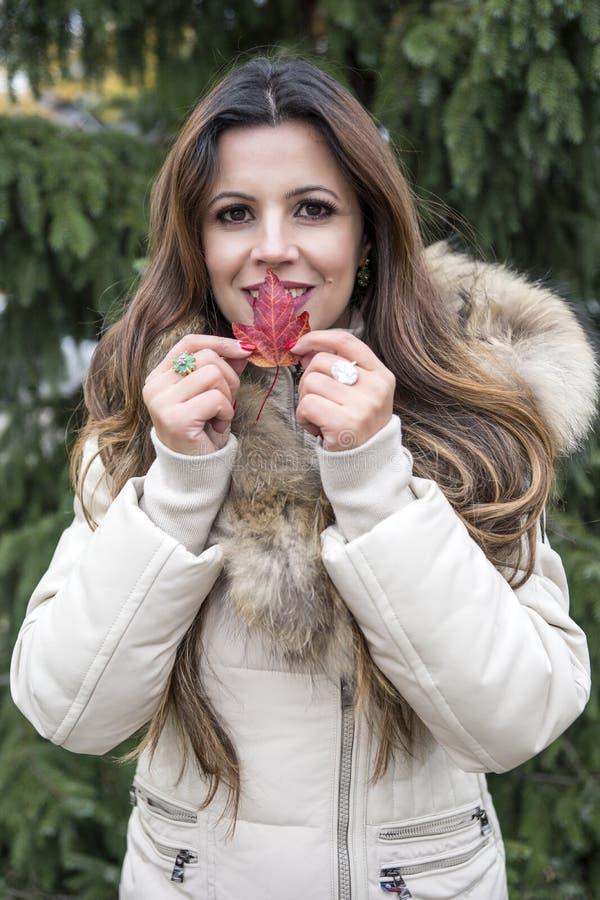 秋天红色枫叶的女孩 秋天折扣 免版税库存图片