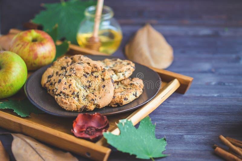 秋天背景特写镜头上色常春藤叶子橙红 曲奇饼,南瓜在木背景留下格子花呢披肩苹果 免版税库存照片