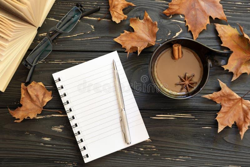 秋天背景特写镜头上色常春藤叶子橙红 咖啡,镜片,开放书,有笔的,槭树笔记本在黑木背景,上面离开 免版税库存照片