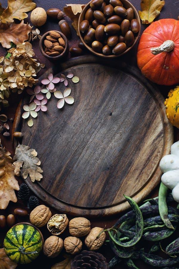 秋天背景用装饰南瓜、橡子、坚果、绿色、秋叶和木板有空间的文本的在黑暗的石头 免版税库存照片