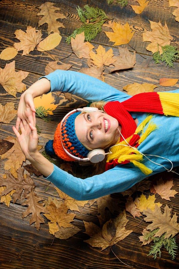 秋天舒适大气 女孩快乐的面孔听在木背景的音乐位置有叶子顶视图 秋天曲调 免版税库存照片