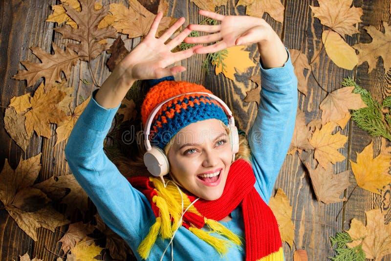 秋天舒适大气 秋天和秋天季节 女孩快乐的面孔听在木背景的音乐位置与叶子上面 免版税库存照片