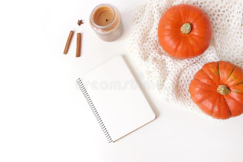 秋天舒适构成 与空白的笔记本的大模型场面 南瓜、蜡烛、肉桂条和被编织的格子花呢披肩在白色 免版税库存图片