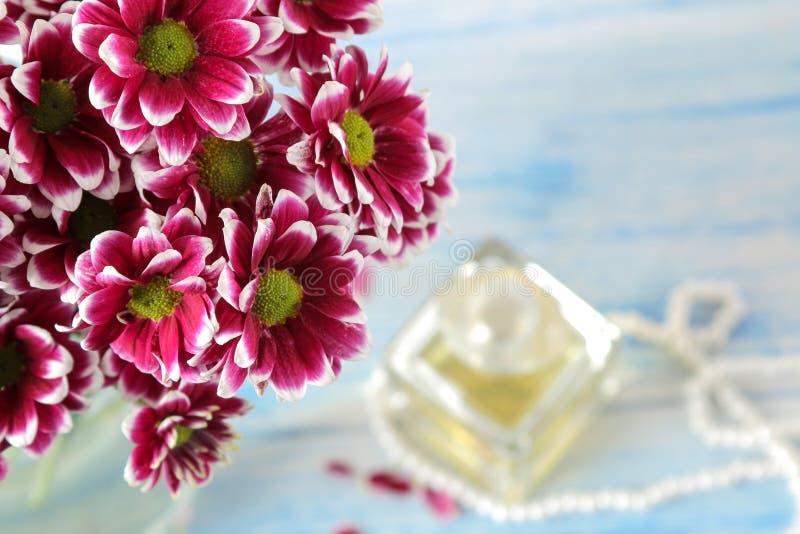 秋天菊花和香水在背景中在一张蓝色木桌上 库存照片