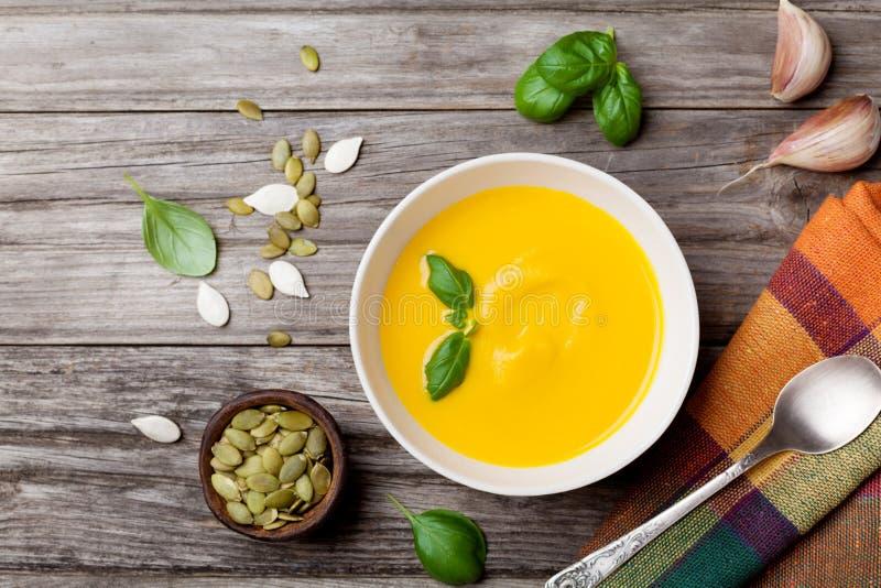 秋天菜或南瓜汤在白色碗在木台式视图 免版税库存图片