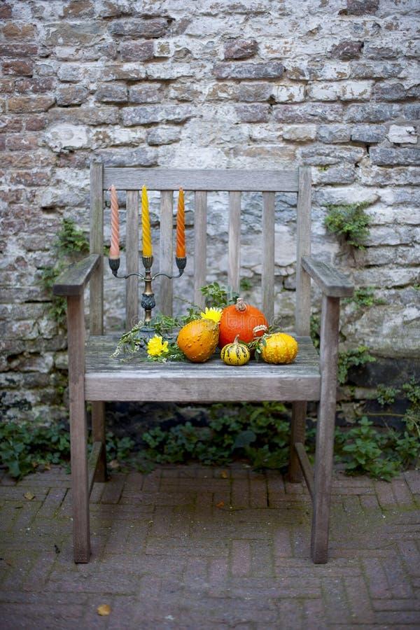 秋天蓝色长的本质遮蔽天空 在木头的秋天果子 感恩 在一把老椅子的秋天菜在庭院里 库存图片