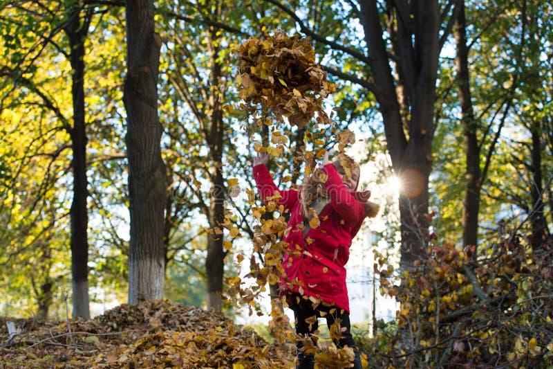 秋天衣裳和时尚概念 儿童白肤金发的长的头发走的秋天公园背景 有敞篷的女孩愉快的穿戴外套 库存照片