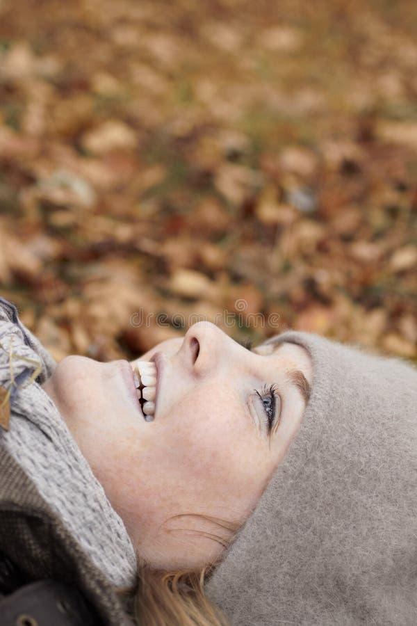 秋天逗人喜爱的喜悦位于的妇女 免版税库存照片