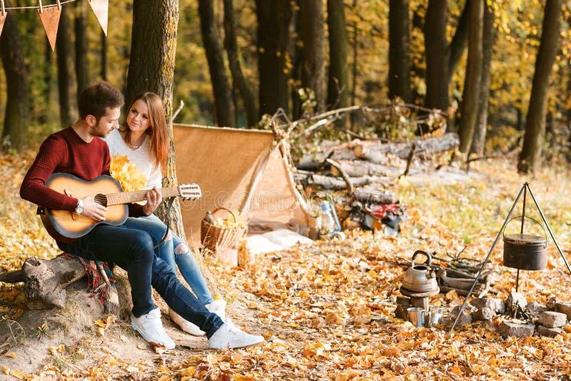 秋天野餐 愉快的加上在帐篷附近的吉他 免版税库存图片