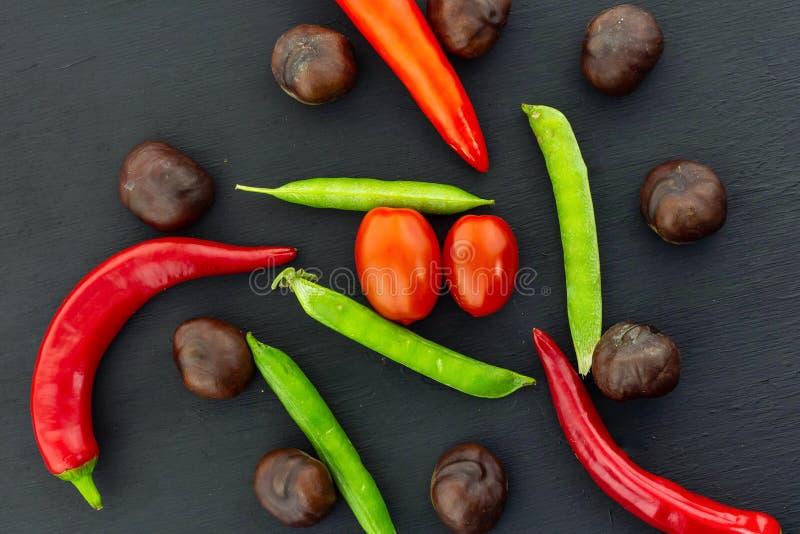 秋天集合荚豌豆荚胡椒红色成熟棕色果子栗子蕃茄樱桃混合菜 库存照片