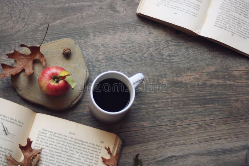 秋天静物画用苹果、咖啡、开放书和叶子在土气木背景,拷贝空间,水平,鸟瞰图 免版税库存图片