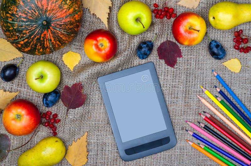 秋天静物画:南瓜、苹果、黄色叶子、片剂和co 免版税库存照片