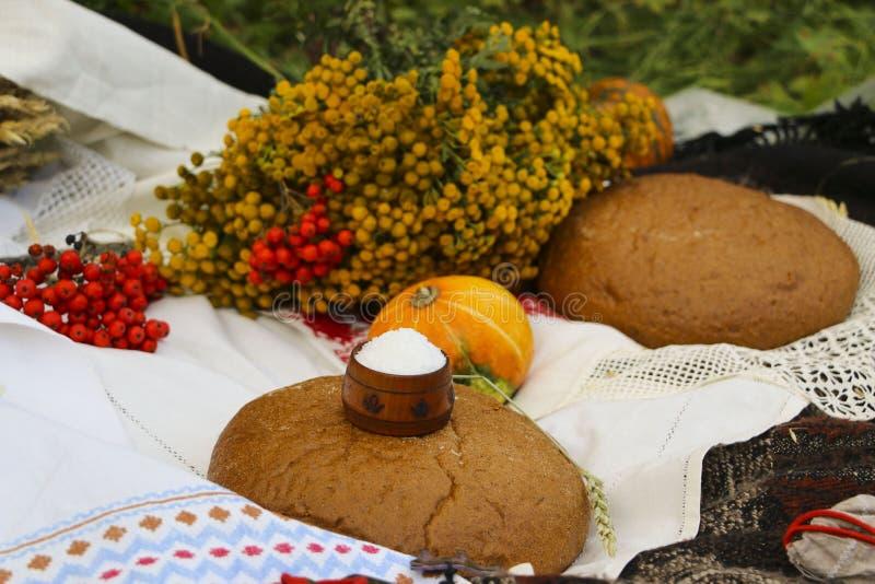 秋天静物画-大面包,南瓜,山脉灰,艾菊,麦子耳朵,盐,在与鞋带的一张白色桌布 免版税图库摄影