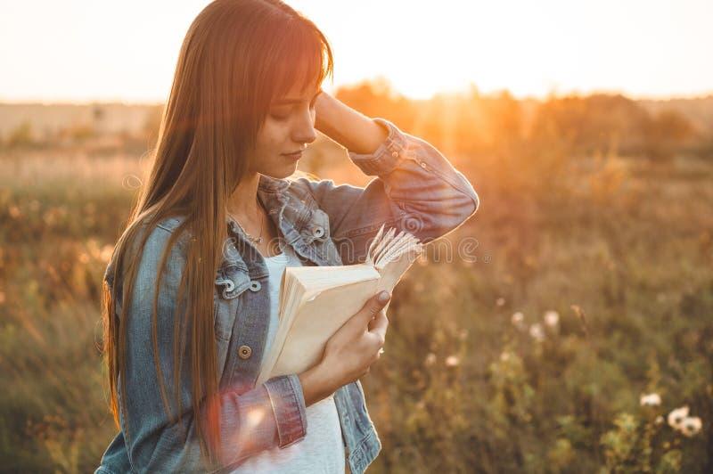 秋天领域的美丽的女孩读书的 女孩坐草,读书 休息和读书 室外读取 免版税图库摄影