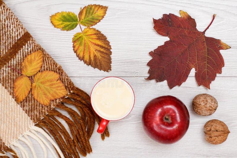 秋天题材 格子花呢披肩、干燥叶子、咖啡,苹果和核桃在木背景 免版税库存照片