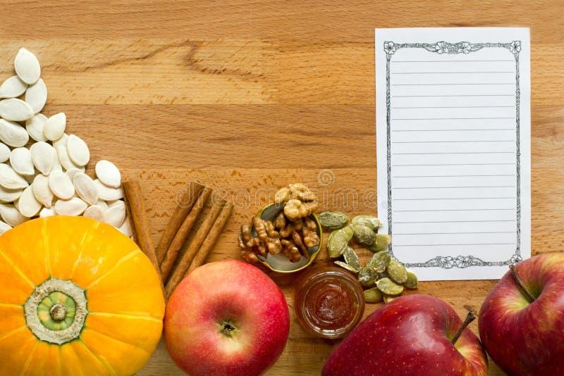 秋天食谱集合 与种子,在一个木切板的苹果的小南瓜有食谱纸的 图库摄影