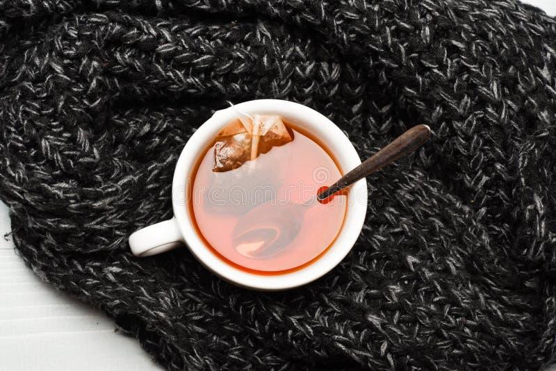 秋天饮料概念 茶杯和被浸洗的袋子茶包裹与被编织的围巾 杯子充满开水,茶袋 免版税库存照片
